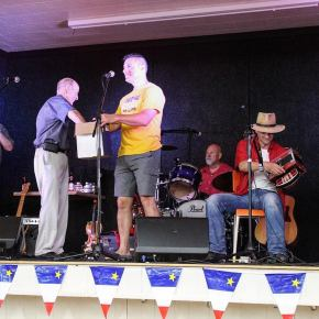 (9) Suite à une démonstration musicale par Jesse Brown du groupe Choupique, c'est M. Baudoin lui-même qui tire le nom de la gagnante de cette boîte que tient Daniel LeBlanc, directeur artistique du Festival acadien de Clare.